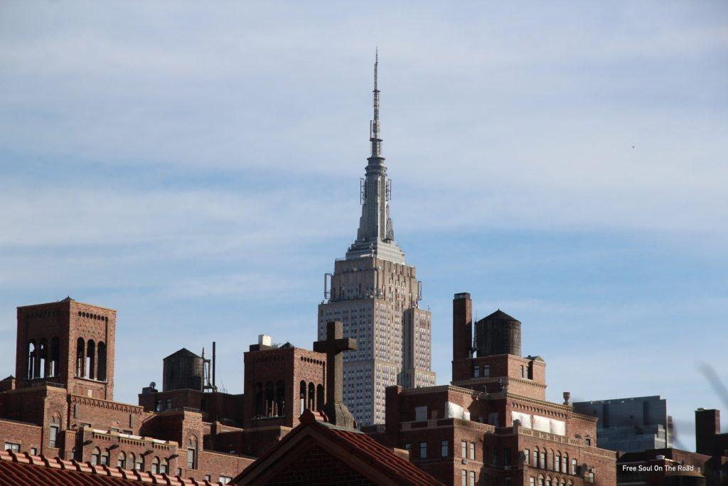 visitare la high line, veduta dell'empire state building tra i tetti dei palazzi lungo la high line